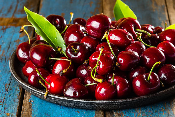 Fresh cherry on black plate stock photo