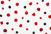 Background from mix berries, close up. Lot of ripe fresh raw cherry, raspberry, red currant and black currant berries scattered on white background. Top view, Flat lay. Beautiful food Wallpaper