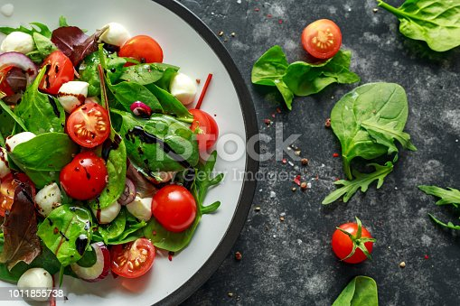 Fresh Cherry Tomato, Mozzarella salad with green lettuce mix and red onion. served on plate. healthy food