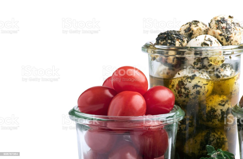 Fresh cherry tomatoes and cheese balls in glass jar stock photo