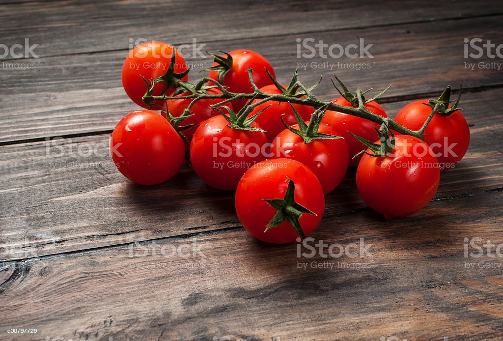 Fresh cherry tomatoes on wood background stock photo