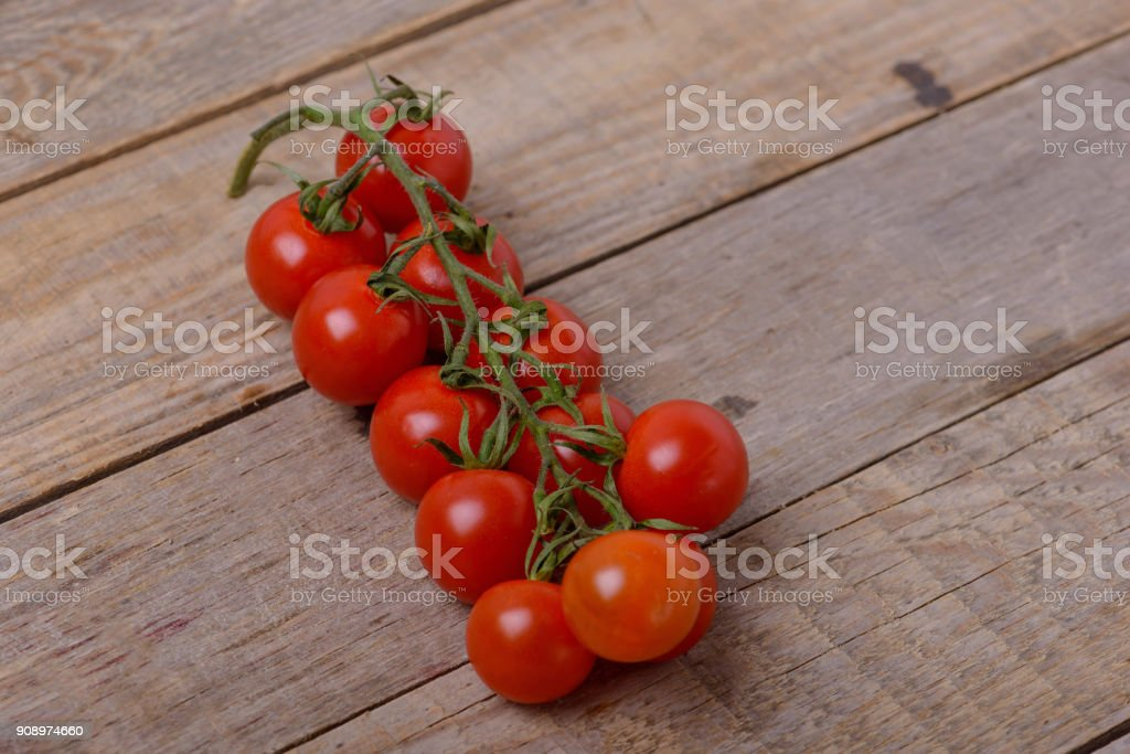 Fresh cherry tomatoes on wooden background stock photo