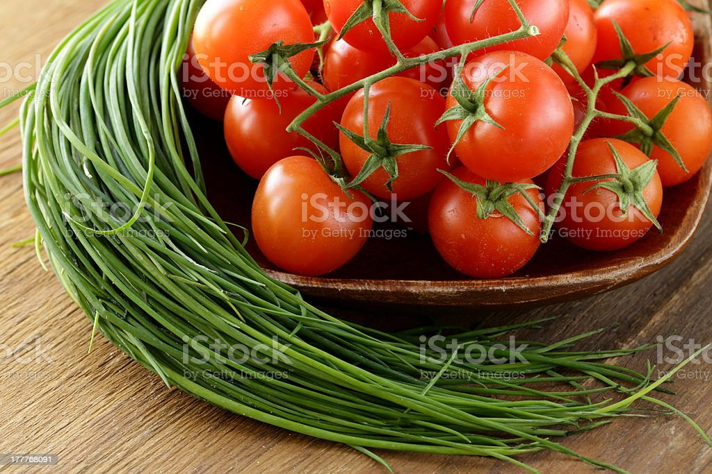 Fresh cherry tomatoes on wooden plate royalty-free stock photo
