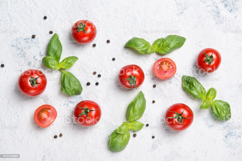 Fresh cherry tomatoes with basil leaves and black pepper on a stone table, vegetable pattern, top view stock photo