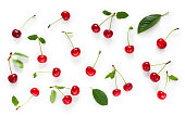 Lot fresh cherry with green leaves isolated on white background, Set of red ripe cherries. Beautiful food Background with scattered cherries. Top view. Flat lay.