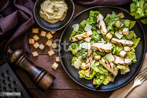 Top view of a  fresh homemade chicken salad on a black plate surrounded by a fork, a napkin, croutons, a bowl with the dressing for seasoning the salad, a pepper shaker and a lettuce. Low key DSLR photo taken with Canon EOS 6D Mark II and Canon EF 24-105 mm f/4L