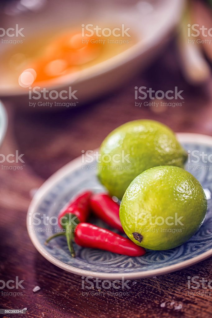 Fresh Chilis and Limes for Preparing Asian Dish stock photo
