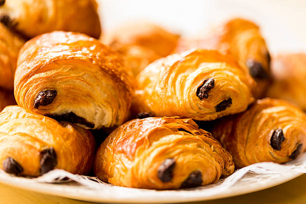 Fresh chocolate croissants on a plate Pile of freshly baked croissants filled with chocolate croissant stock pictures, royalty-free photos & images