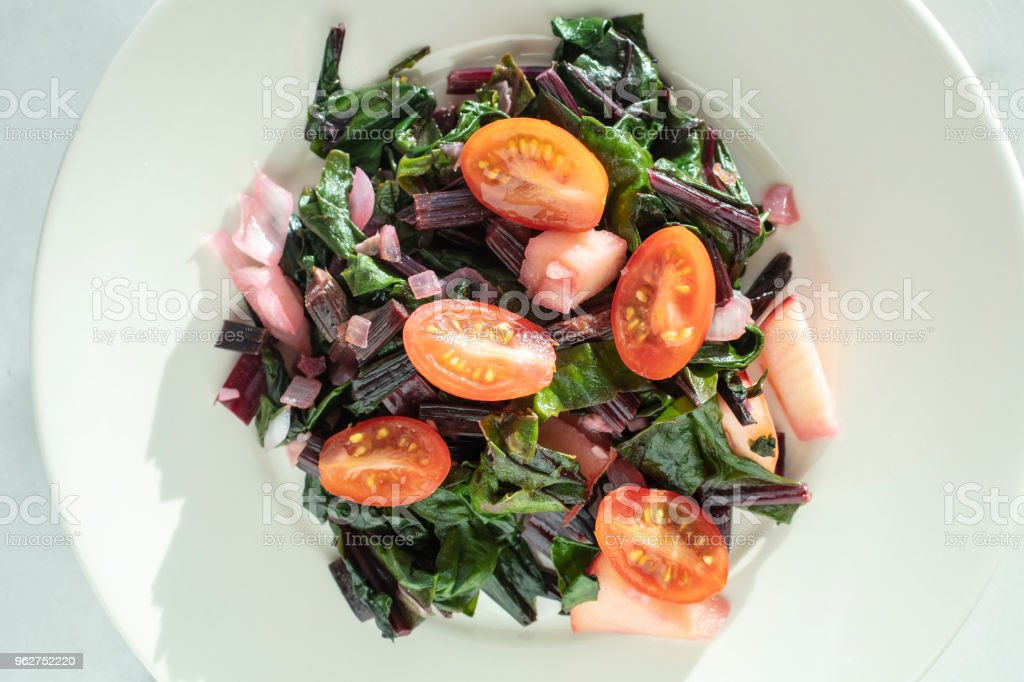 Fresh chopped beet, tomatoe and onion sauteed salad served on a white plate - Foto stock royalty-free di Alimentazione sana