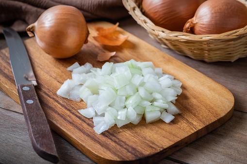 Fresh chopped onions on wooden cutting board