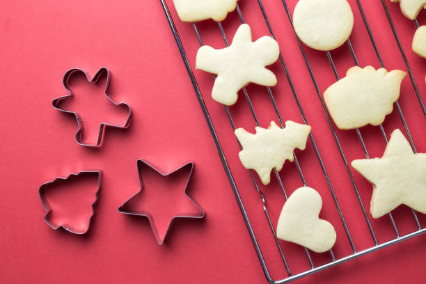 Fresh christmas cookies on oven rack and molds isolated on red. Flat lay of christmas cookies on oven grate and cookie cutters against red background minimal creative holiday and food concept. cookie cutter stock pictures, royalty-free photos & images