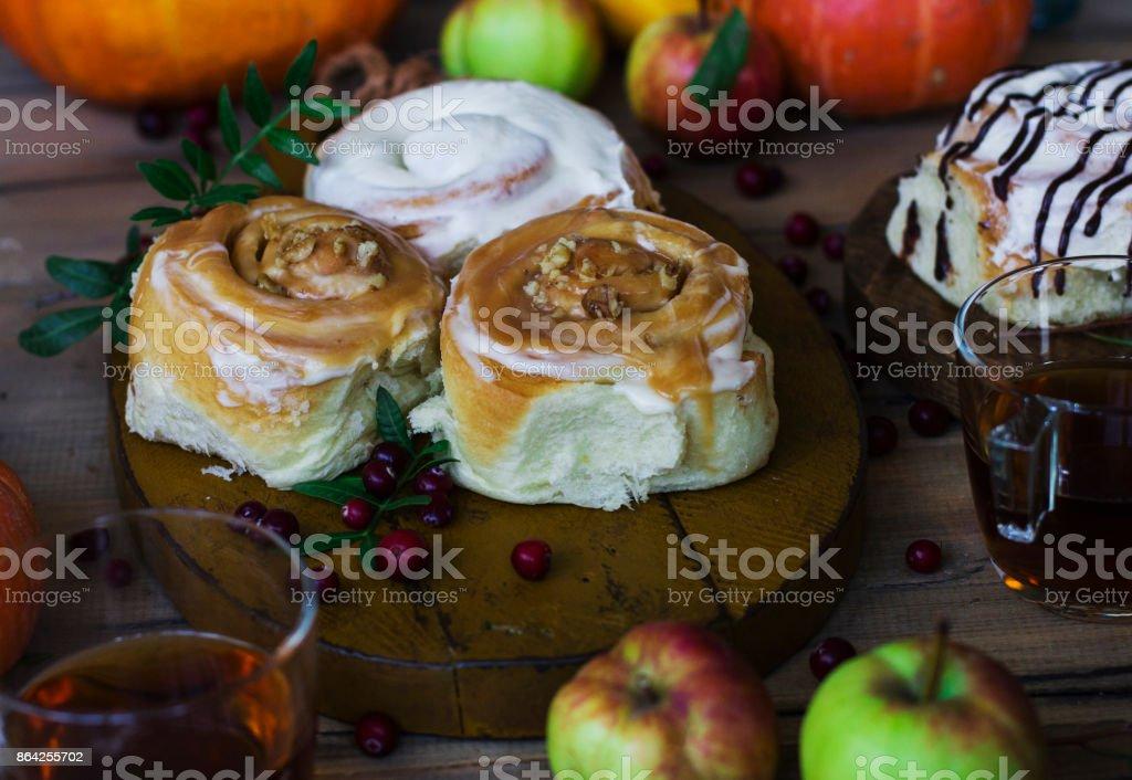 Fresh cinnamon rolls with tea, pumpkins and apples royalty-free stock photo