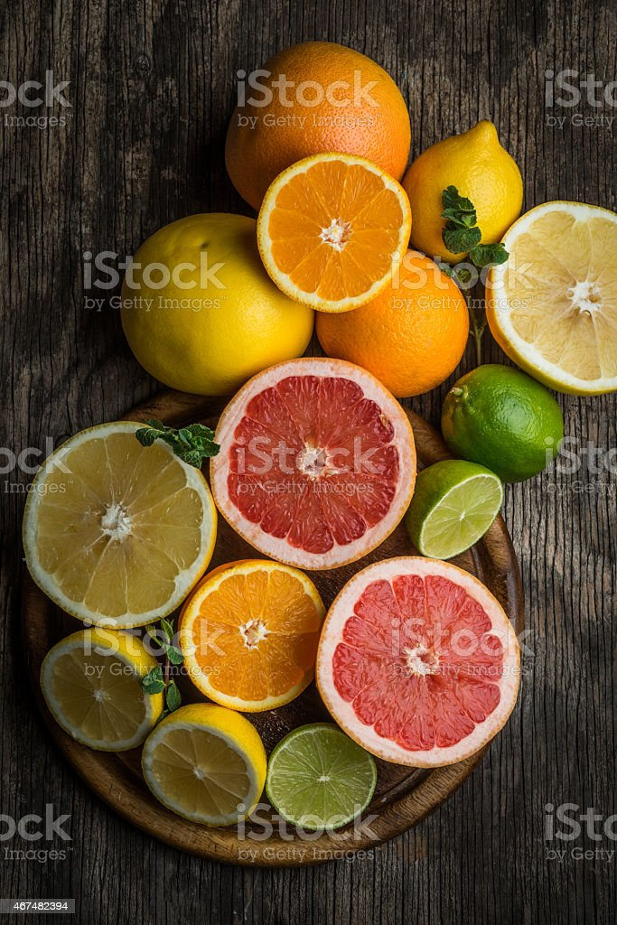 Fresh citrus fruits on rustic wooden background, top view stock photo