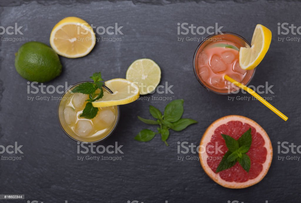 Fresh citrus juices on dark stone plate stock photo