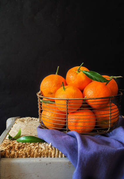Fresh clementines, in a metellic basket on black background - foto stock