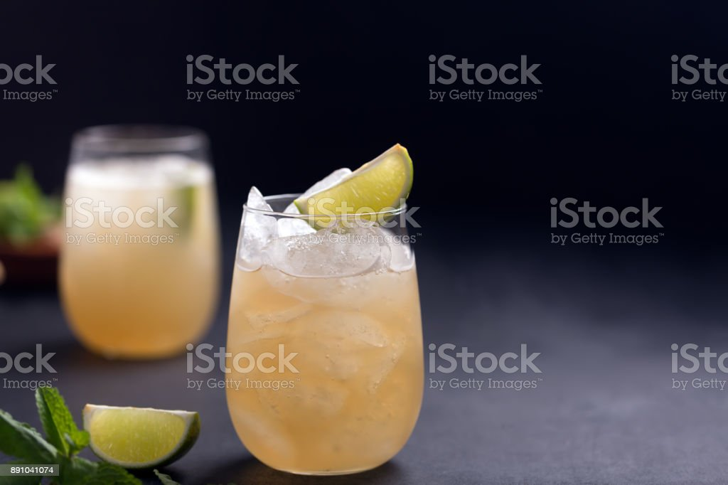 Fresh cocktail prepared with ginger beer, lime and ice. Black background stock photo