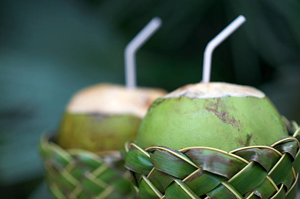 Fresh Coco Gelado Drinking Coconuts in Woven Basket Fresh Brazilian coco gelado drinking coconuts in woven palm baskets rest on weathered wooden table against green jungle background gelado stock pictures, royalty-free photos & images