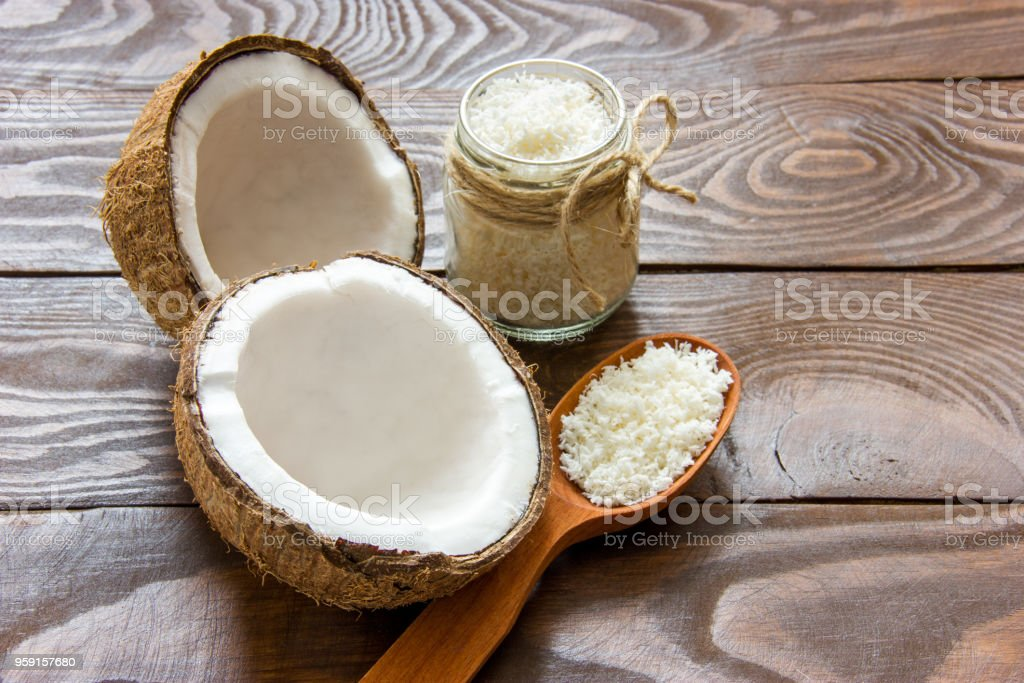 fresh coconut cracked in half on a wooden table with coconut chips in a glass jar and in a wooden spoon with a place for writing stock photo
