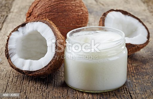 istock Fresh coconuts and a jar of coconut oil on a wooden table 466130802