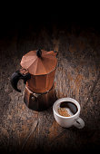 Fresh coffee in white porcelain mug and old rustic used moka pot arrangement on dark old wooden rustic table in studio