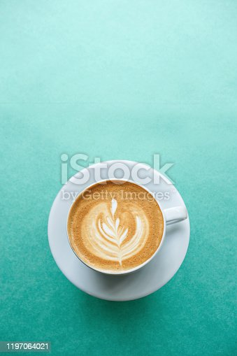 Close up of a cup of fresh cappuccino coffee on a mint background in minimal style.