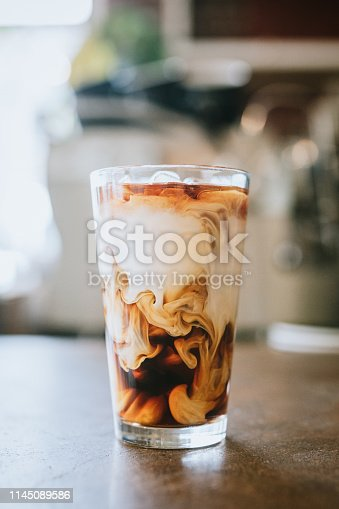 A cool refreshing glass of iced single origin coffee to enjoy on a hot summer day.  Vertical image.