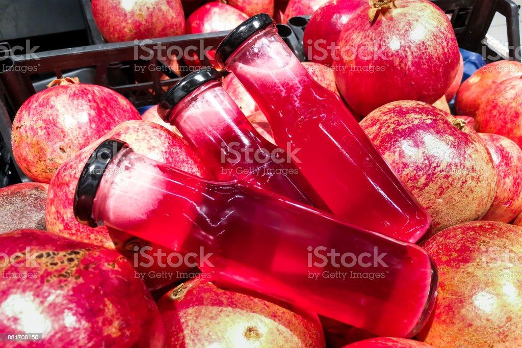 Fresh cold pressed organic pomegranate juice against pomegramate stock photo