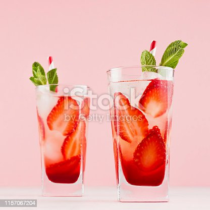 Fresh cold strawberry cocktail with green mint, ice, straw on soft light pastel pink background, square.
