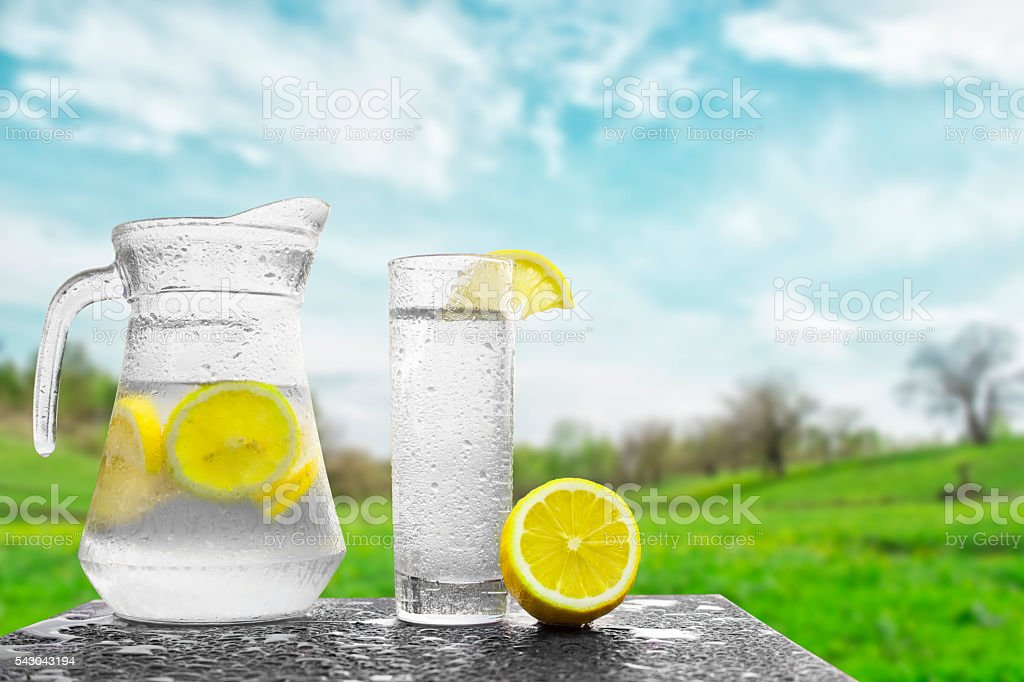Fresh cold water with lemon and ice in a pitcher. stock photo