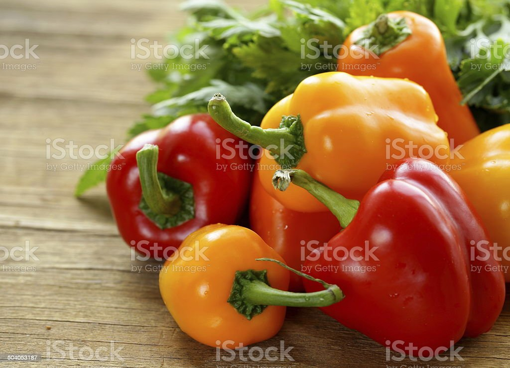 fresh colorful bell peppers on a wooden background stock photo