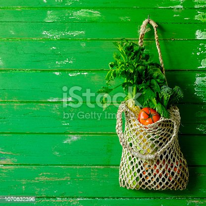 istock Fresh colorful salad vegetables in a reusable string bag hanging by a hook on an old green weathered wood plank wall background. 1070832396