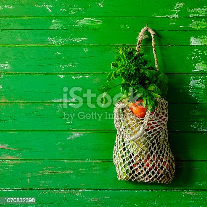 istock Fresh colorful salad vegetables in a reusable string bag hanging by a hook on an old green weathered wood plank wall background. 1070832398