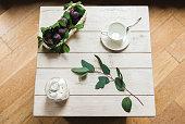 A fresh composition of plums and ceramic cup on a white wooden table