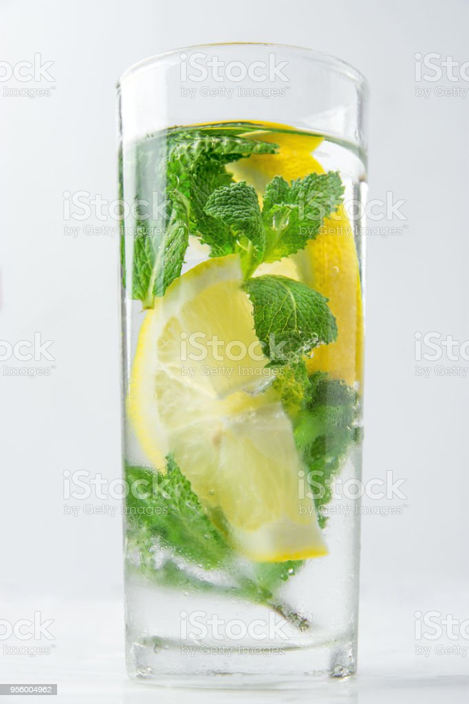 Fresh Cool Infused Detox Water with Ripe Organic Sliced Lemons Mint in Tall Frosty Glass. White Background. Healthy Drink Detox Summer Refreshment. Copy Space stock photo