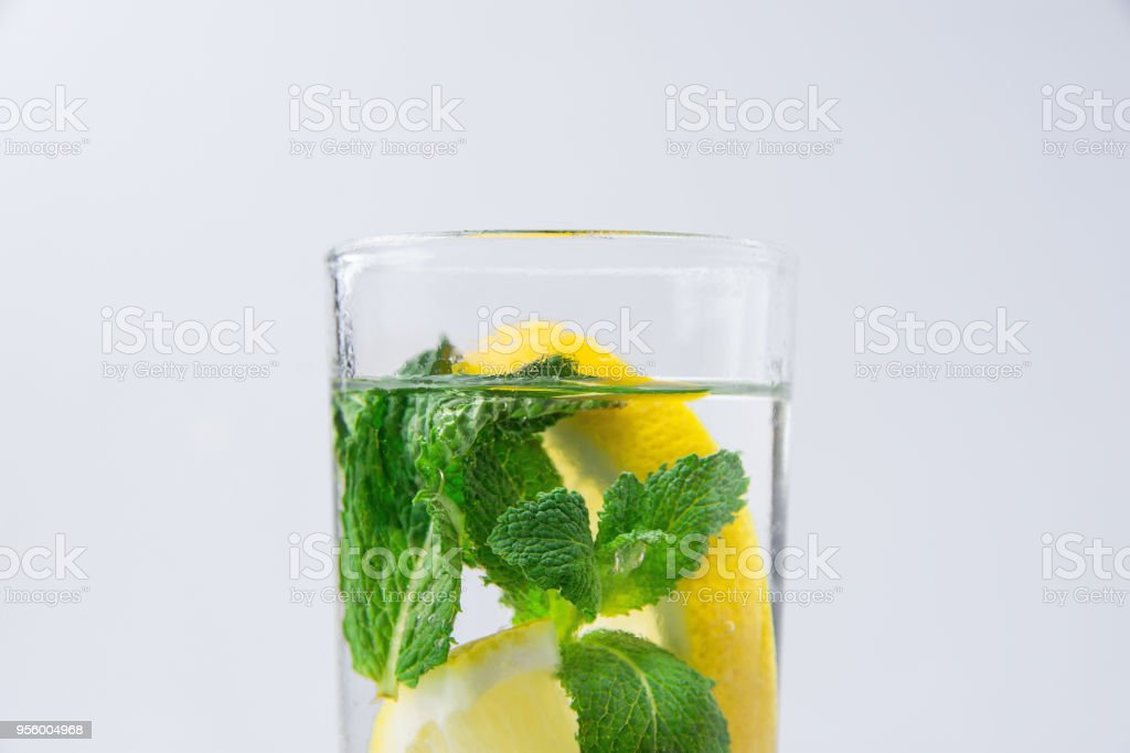 Fresh Cool Infused Detox Water with Ripe Organic Sliced Lemons Mint in Tall Glass. White Background. Healthy Drink Detox Summer Refreshment. Copy Space stock photo
