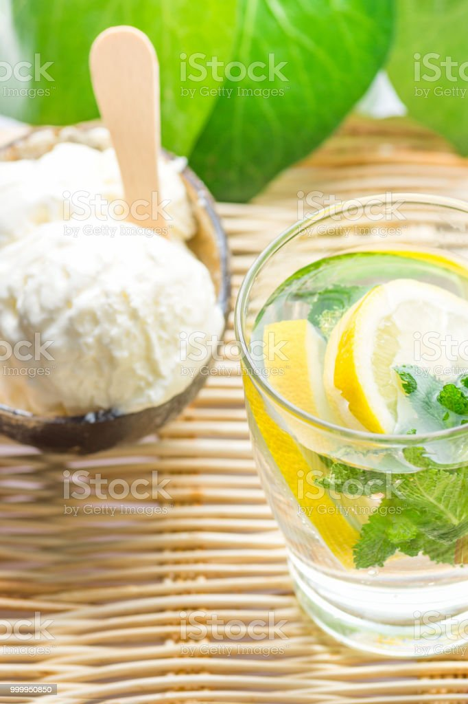 Fresh Cool Infused Detox Water with Ripe Organic Sliced Lemons Mint in Frosty Glass Ice Cream in Coconut Bowl on Rattan Table. Tropical Plants Background. Healthy Drink Dessert Summer Refreshment stock photo