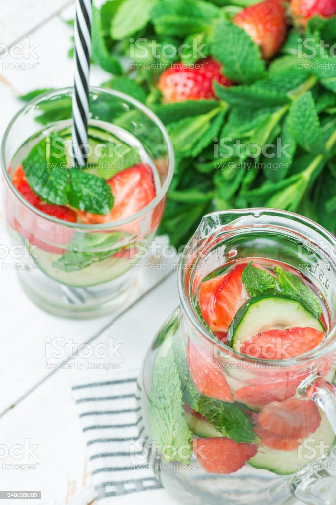Fresh Cool Infused Detox Water with Ripe Organic Strawberries Sliced Cucumbers Mint in Glass and Jug. White Plank Wood Background. Healthy Drink Detox Summer Refreshment. Copy Space stock photo