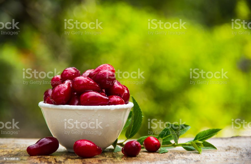 Fresh cornel berries in a white bowl on an old wooden table in the garden. Red berries. stock photo