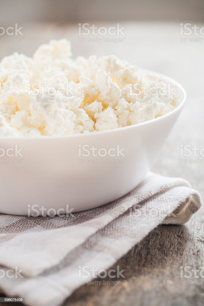 fresh cottage cheese in a white bowl on  wooden background royalty-free stock photo