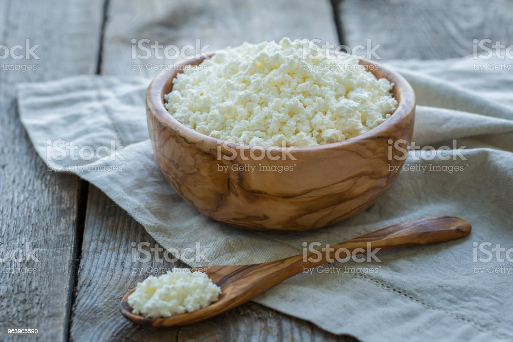 Fresh cottage cheese in a wooden bowl on a linen napkin and a wooden old background - Royalty-free Backgrounds Stock Photo
