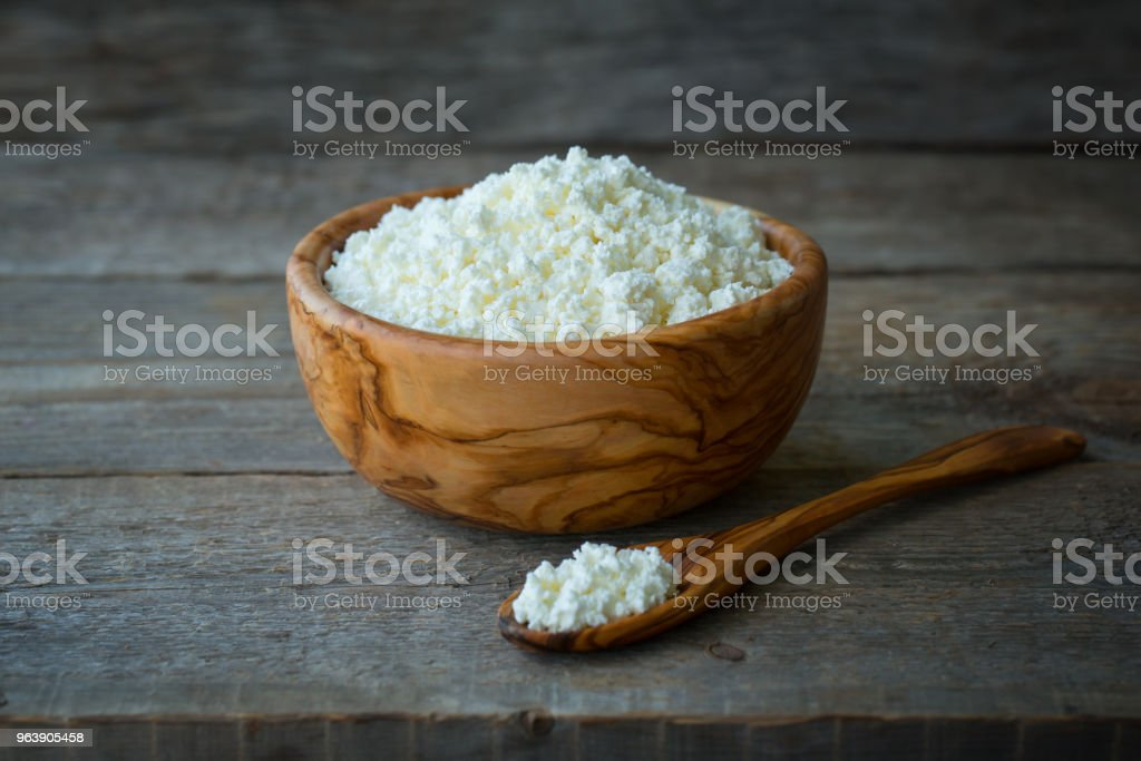 Fresh cottage cheese in a wooden bowl with a spoon on a wooden old background - Royalty-free Backgrounds Stock Photo