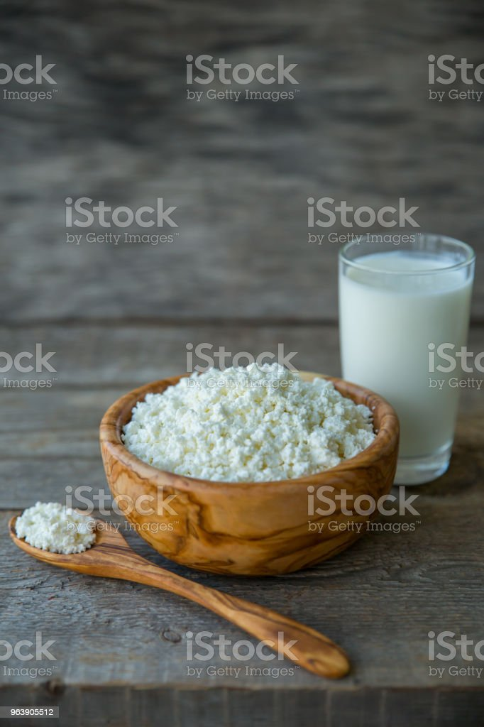 Fresh cottage cheese in a wooden bowl with a spoon with a glass of milk on a wooden old background - Royalty-free Backgrounds Stock Photo