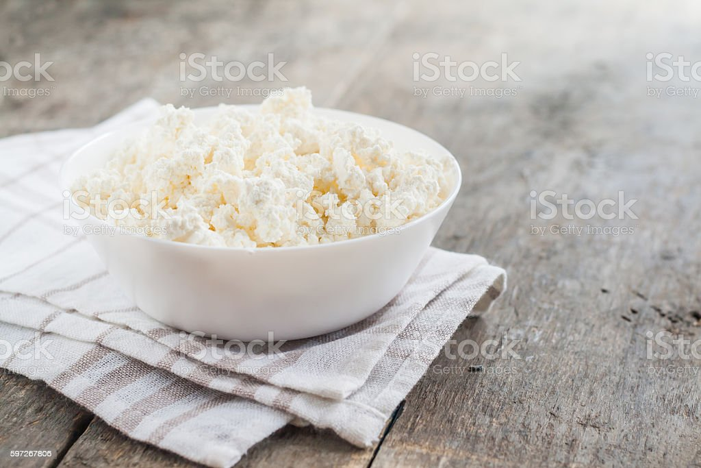 fresh cottage cheese in  white bowl on a wooden background Lizenzfreies stock-foto