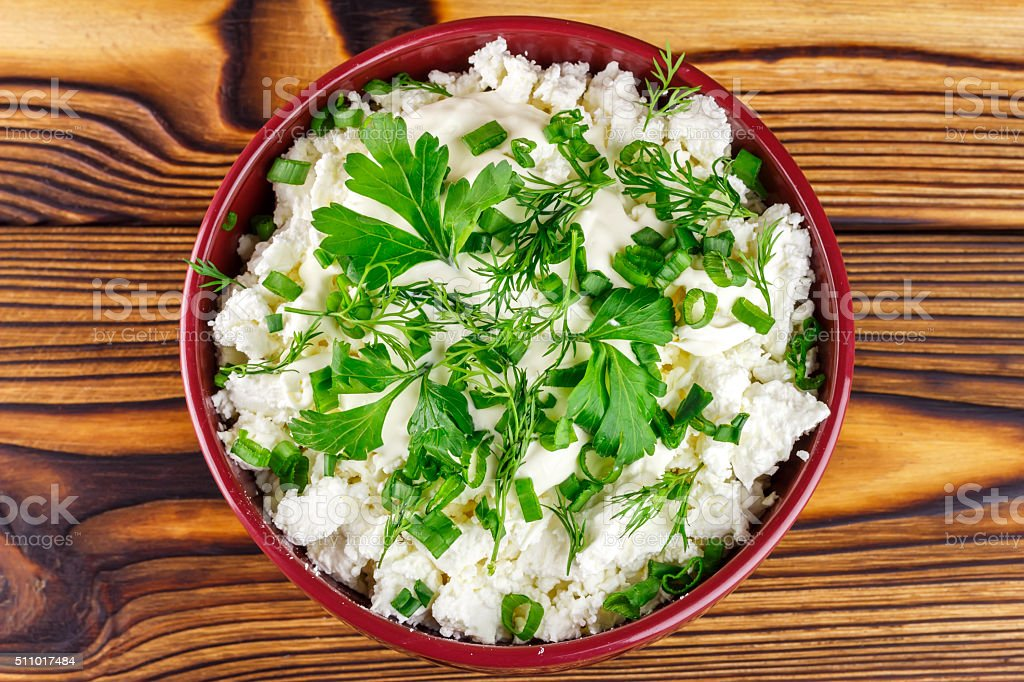 Fresh cottage cheese, sour cream, dill, parsley, onion in bowl stock photo