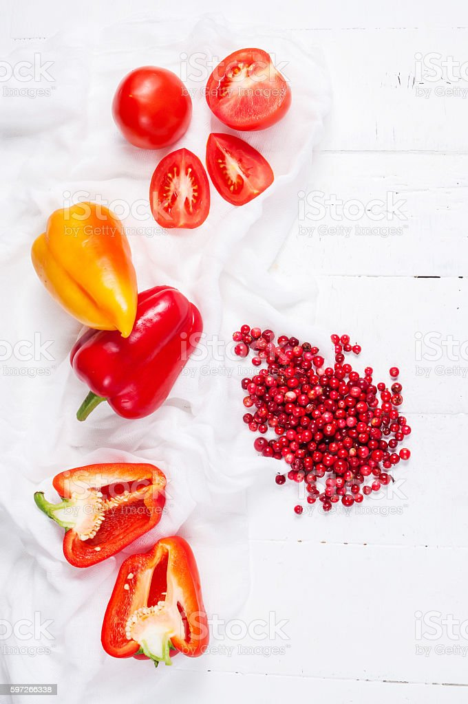 Fresh cowberry, tomatoes and pepper on a white wooden table royalty-free stock photo