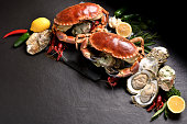 Fresh crabs and seafood arranged on stone background