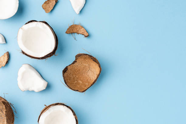 Fresh cracked coconut on blue background with copyspace. Flat lay stock photo