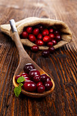Fresh cranberries in burlap bag and spoon on wooden table. Culinary fruit eating.