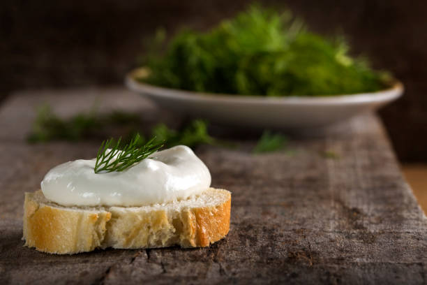 Fresh cream cheese on bread slice with dill on wood stock photo