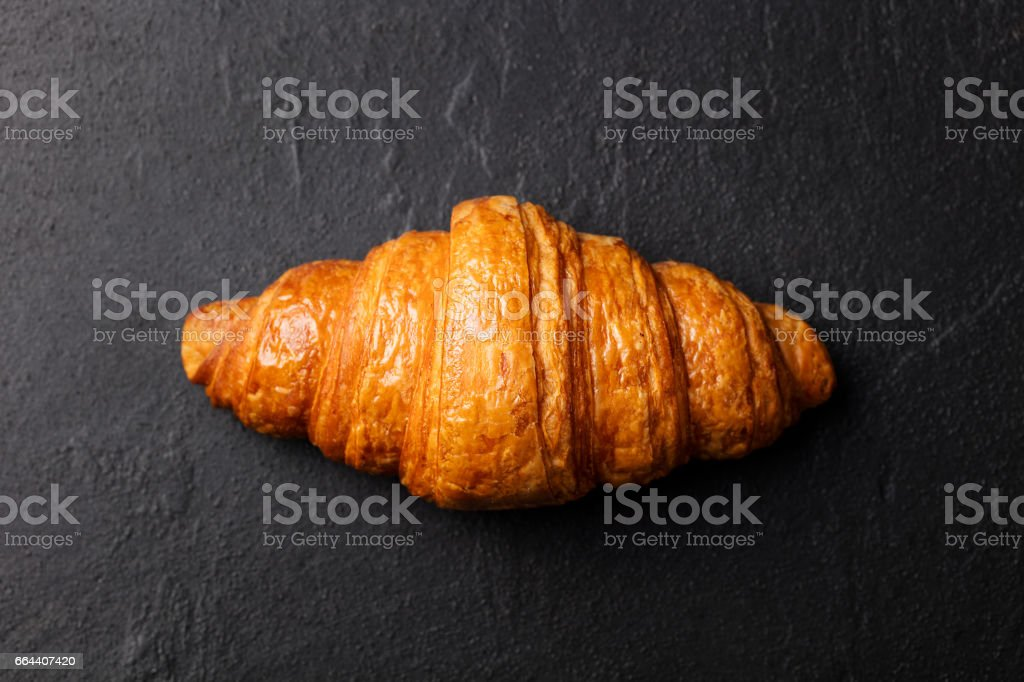 Fresh croissant on a black slate background. Top view. Copy space stock photo